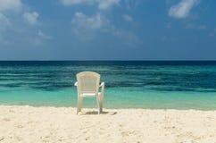 Vit stol på vit sand av den tropiska stranden mot turkosvattnet av Indiska oceanen, Maldiverna Fotografering för Bildbyråer