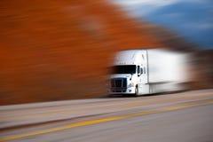 Vit stor halv lastbil på vägen på suddig färgbakgrund Arkivfoton