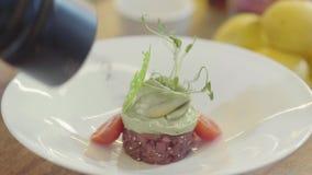 Vit stor platta med att förbluffa garnering av en maträtt Rund form av den lilla cutted tonfiskfisken, överst gräsplansause och g stock video