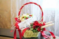 Vit strumpeband av bruden i en bukett för röda rosor royaltyfri foto