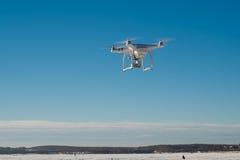 Vit surrkvadrathelikopter med flyg i den blåa himlen Arkivfoton