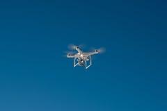 Vit surrkvadrathelikopter med flyg i den blåa himlen Arkivbilder