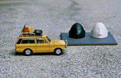 Vit svart vänd mot nytto- bil som parkeras bredvid en grav Arkivfoton
