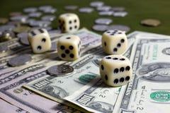 Vit tärnar, mynt och amerikanska dollarsedlar på den gröna tabellen Royaltyfri Foto