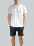 Vit t-skjorta och svartkortslutningar på en mall för ung man på grå färger b royaltyfria foton
