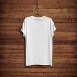 Vit t-skjorta på den wood väggen Royaltyfri Fotografi
