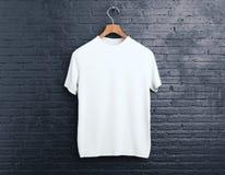 Vit t-skjorta på tegelstenbakgrund royaltyfria foton