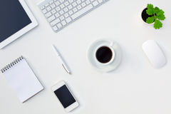 Vit tabell för kontorsskrivbord med den elektroniska grejer och brevpapperkaffekoppen och blomman Royaltyfria Foton