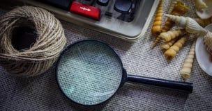 Vit tabell för kontorsskrivbord med den gamla skrivmaskinen, rep, snäckskal och förstoringsglaset Bästa sikt med kopieringsutrymm Royaltyfri Foto