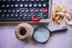 Vit tabell för kontorsskrivbord med den gamla skrivmaskinen, rep, snäckskal och förstoringsglaset Bästa sikt med kopieringsutrymm Royaltyfri Fotografi