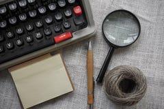 Vit tabell för kontorsskrivbord med den gamla skrivmaskinen, rep, snäckskal och förstoringsglaset Bästa sikt med kopieringsutrymm Arkivbilder