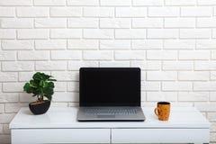 Vit tabell nära den vita väggen Tom arbetsplats i rummet Vit bakgrund Arkivfoto