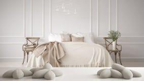 Vit tabell, skrivbord eller hylla med fem mjuka vitkuddar i formen av stjärnor eller blommor, över suddigt klassiskt sovrum fotografering för bildbyråer