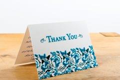 Vit tackar dig att card med blåa bokstäver med anmärkningen som är skriftlig vid handen Arkivfoton