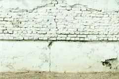 Vit tegelstenvägg för Grunge med den dåliga fundamentgrunden för spricka och skadad murbruk Royaltyfri Fotografi