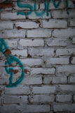 Vit tegelstenvägg med grafitti Fotografering för Bildbyråer