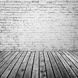 Vit tegelstenvägg och grått trägolv Arkivfoton