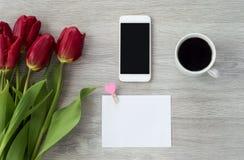Vit telefon med ett ark av pappers- lögner på en vit trätabell med en kopp kaffe och röda blommor arkivfoton