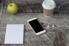 Vit telefon med hörlurar, kaffe, notepaden och det gröna äpplet på tabellen Arbete hemma frilans royaltyfri foto