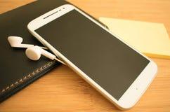 Vit telefon och hörlurar på tabellen fotografering för bildbyråer