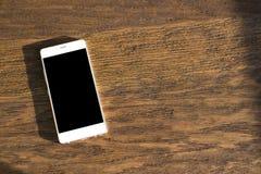 Vit telefon på en trätabell Royaltyfri Foto