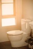Vit toalett i det moderna hemmet, vit toalettbunke i lokalvårdrum som spolar flytande i toalett, privat toalett i modernt rum Royaltyfria Bilder
