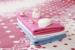 Vit toaletttvål och dekor mot bakgrunden av rosa frottéhanddukar royaltyfria foton
