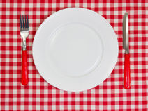 Vit tom ren platta på röd borddukbakgrund med dishwa Royaltyfri Fotografi