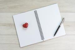 Vit tom sida för öppningsanmärkningsbok med pennan och älskvärd röd cera Fotografering för Bildbyråer