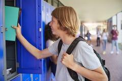 Vit tonårs- skolpojke som använder skåpet i skolakorridor arkivbilder