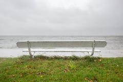 Vit träbänk på kusten av lagun på lugna regnig dag i spottade Curonian, Litauen arkivfoton