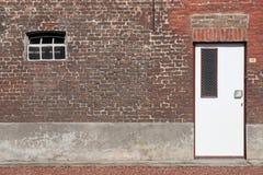 Vit trädörr i en vägg för röd tegelsten Arkivfoton