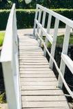 Vit träfotbro över en smal flod på en solig dag Royaltyfria Foton