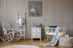 Vit trägungstol med kudden bredvid scandinavian stege, byrån och vaggan, kopieringsutrymme på väggen med gulligt royaltyfria foton