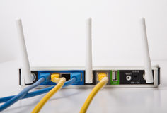 Vit trådlös Router med blått- och gulingkablar Arkivfoton