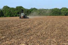 Vit traktor som brukar fältet Arkivbild