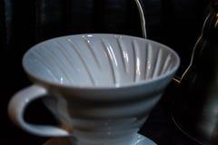 Vit tratt Pourover på en svart bakgrund för förberedelse av kaffe vid en alternativ metod Arbeta baristaen i coffee shop arkivfoto