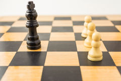 Vit tre pantsätter mot svart konung Royaltyfri Foto