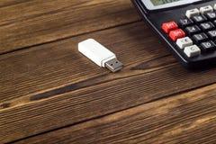 Vit USB exponeringsdrev och räknemaskin på en träbakgrund, närbild, grej royaltyfri foto