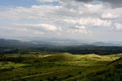 Vit väderkvarn, blå himmel, vita moln, gröna berg och vatten arkivbilder
