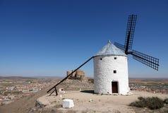 Vit väderkvarn och slott på kullen i Consuegra, Spanien arkivbilder