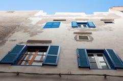 Vit vägg med blåa fönster Arkivbild