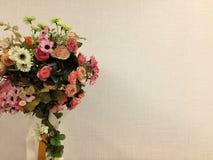 Vit väggbakgrund med den plast- blomman arkivbild