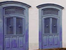 Vit väggfasad med två blåa trädörrar arkivbilder