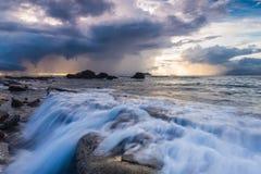 Vit våg och den steniga kustsoluppgången Royaltyfri Foto