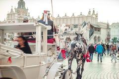 Vit vagn med turisten på marknadsfyrkant i Krakow, Polen Royaltyfria Bilder