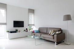 Vit vardagsrum med taupesoffan Fotografering för Bildbyråer