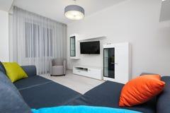 Vit vardagsrum med TVuppsättningen, stol och grå färgsoffan Royaltyfri Bild