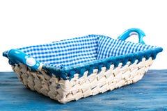 Vit vide- korg av bröd med den rutiga torkduken på blå backgr Royaltyfri Fotografi