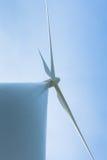 Vit vindturbin som frambringar elektricitet på blå himmel Arkivfoto